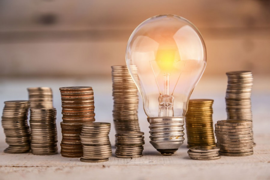 energy efficient light bulb and pile of coins
